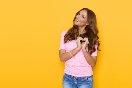 shaped hands: Beautiful smiling young woman in pastel pink shirt and jeans showing heart shaped hands. Waist up studio shot on yellow background.