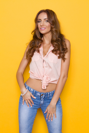 pink posing: Beautiful young woman in pastel pink shirt and jeans posing against yellow background. Stock Photo
