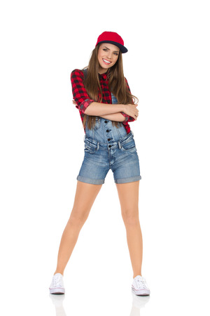 legs apart: Woman in red lumberjack shirt, jeans shorts, white sneakers and fullcap posing with arms crossed. Full length studio shot isolated on white. Stock Photo