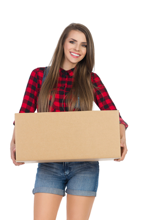 lumberjack shirt: Smiling young woman in red lumberjack shirt and jeans shorts holding cardboard box. Three quarter length studio shot isolated on white.