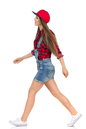 lumberjack shirt: Woman in red lumberjack shirt, jeans shorts and white sneakers walking and looking away. Side view. Full length studio shot isolated on white.