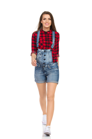 striding: Woman in red lumberjack shirt, jeans dungarees shorts and white sneakers walking towards the camera. Front view. Full length studio shot isolated on white.