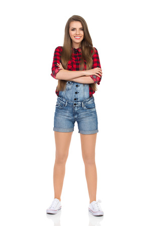 dungarees: Woman in red lumberjack shirt, jeans dungarees shorts and white sneakers with arms crossed. Full length studio shot isolated on white.