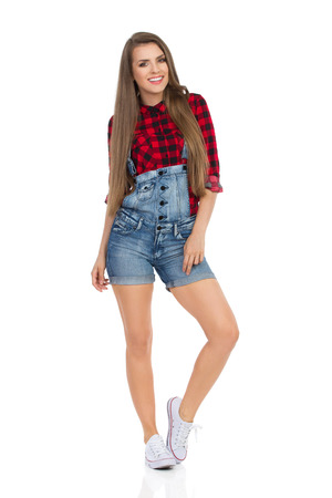 dungarees: Smiling young woman in red lumberjack shirt, jeans shorts and white sneakers standing relaxed and looking at camera. Full length studio shot isolated on white.