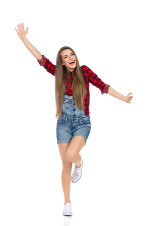 lumberjack shirt: Woman in red lumberjack shirt, jeans dungarees shorts and white sneakers standing on one leg with arms outstretched and shouting. Full length studio shot isolated on white.
