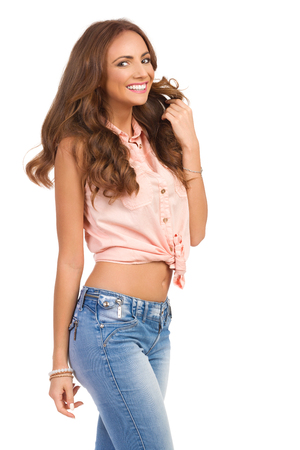 Smiling attractive woman in pastel pink shirt and jeans posing and looking at camera, Three quarter length studio shot isolated on white. Stock Photo