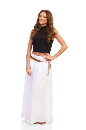 6bfd36294a  62089721 - Mujer atractiva en falda blanca larga y top negro posando con  la mano en la cadera sonriente