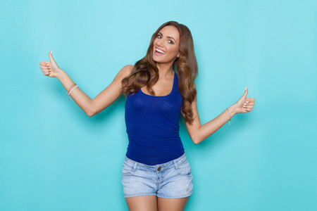 Smiling beautiful young woman in blue tank top and jeans shorts showing thumbs up. Three quarter length studio shot on turquoise background.