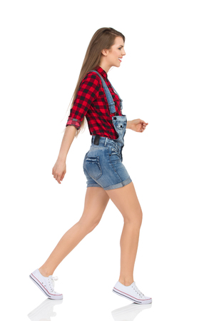 Woman in red lumberjack shirt, jeans dungarees shorts and white sneakers walking tiptoe and looking away. Side view. Full length studio shot isolated on white.