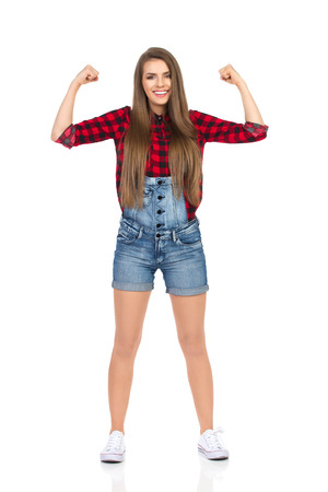 lumberjack shirt: Confident smiling woman in red lumberjack shirt, jeans dungarees shorts and white sneakers standing with legs apart and flexing muscles. Full length studio shot isolated on white. Stock Photo
