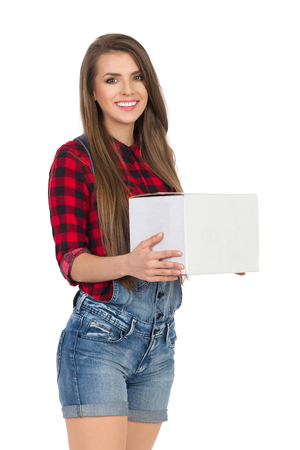 Smiling young woman in red lumberjack shirt and jeans dungarees shorts holding white box. Three quarter length studio shot isolated on white.