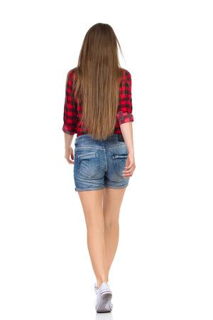 Vrouw in rood houthakker shirt, jeans broek en witte sneakers weglopen. Achteraanzicht. Full length studio shot geïsoleerd op wit. Stockfoto