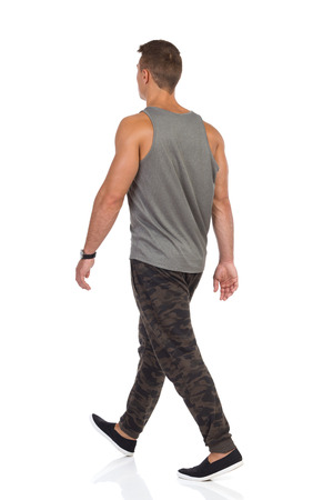 Young man walking in tracksuit pants with camo, gray tank top and black sneakers. Rear view. Full length studio shot isolated on white.