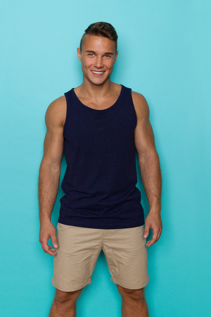Handsome young man in blue tank top and beige shorts, standing relaxed, looking at camera and smiling. Three quarter length studio shot on turquoise background.