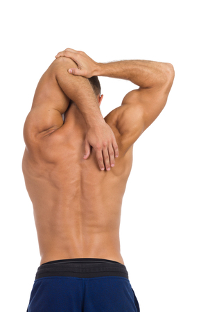 half naked: Half naked fit man showing how to stretch triceps, Rear view. Waist up studio shot isolated on white. Stock Photo