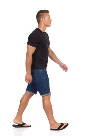 striding: Young man walking in black shirt, jeans shorts and black sandals. Side view. Full length studio shot isolated on white. Stock Photo