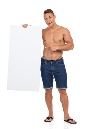 half naked: Half naked fit man in jeans shorts and black flip-flops standing, holding white placard, pointing and shouting, Full length studio shot isolated on white.