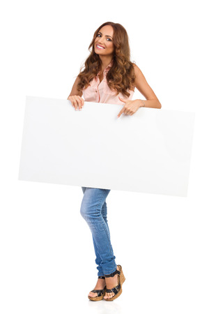 big cork: Smiling attractive woman in pink shirt, jeans, and cork high heels, standing holding big white poster and pointing. Full length studio shot isolated on white.