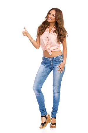 Smiling attractive woman in pink shirt, jeans and cork high heels showing thumb up and looking at camera, Full length studio shot isolated on white.