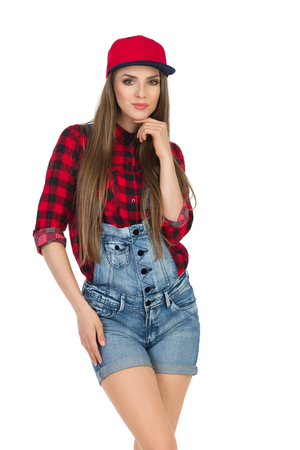 dungarees: Woman posing in red lumberjack shirt, jeans dungarees shorts and fullcap. Three quarter length studio shot isolated on white.