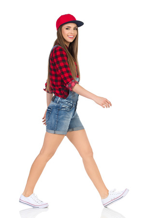 lumberjack shirt: Woman in red lumberjack shirt, jeans shorts and white sneakers walking and looking at camera. Side view. Full length studio shot isolated on white.