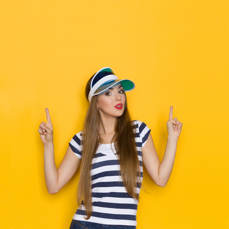 waist shot: Young woman in blue striped shirt and blue sun visor pointing up. Waist up studio shot on yellow background.