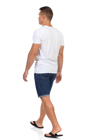 Young man walking in white shirt, jeans shorts and black sandals. Rear side view. Full length studio shot isolated on white. Stock Photo