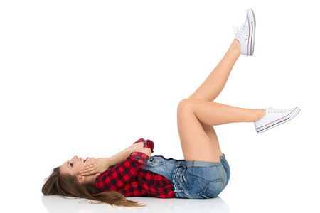 Shouting young woman in red lumberjack shirt, jeans shorts and white sneakers lying down on her back on a floor holding head in hands and looking away. Full length studio shot isolated on white. Stock Photo