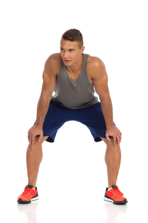 Young fit man in blue shorts, gray tank top and orange sneakers crouching and looking away Front view. Full length studio shot isolated on white.