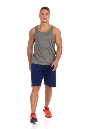 Young man in blue shorts, gray tank top and orange sneakers, walking and looking at camera. Front view. Full length studio shot isolated on white. Stock Photo