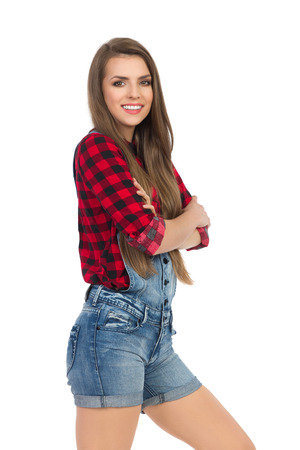 dungarees: Woman in red lumberjack shirt and jeans dungarees posing with arms crossed. Three quarter length studio shot isolated on white. Stock Photo