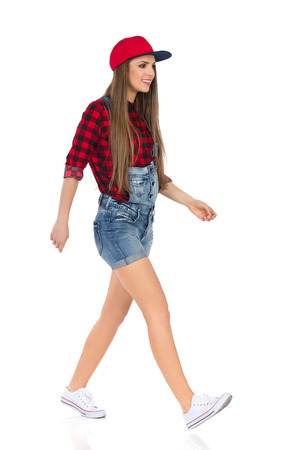 Woman in red lumberjack shirt, jeans dungarees shorts white sneakers and full cap walking and looking away. Front, side, front view. Full length studio shot isolated on white.