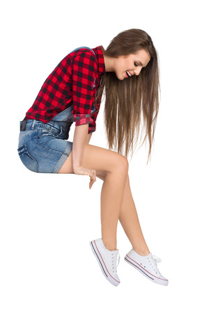 lumberjack shirt: Smiling young woman in red lumberjack shirt, jeans shorts and white sneakers sitting on a top and looking down. Side view. Full length studio shot isolated on white. Stock Photo