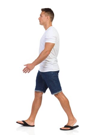 Young man walking in white shirt, jeans shorts and black sandals. Side view. Full length studio shot isolated on white.
