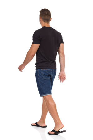 Young man walking in black shirt, jeans shorts and black sandals. Rear side view. Full length studio shot isolated on white. Stock Photo