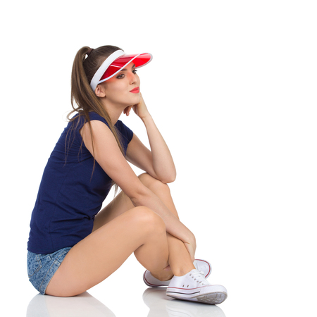 visor: Pensive young woman in blue shirt, jeans shorts and red sun visor cap sitting on a floor with legs crossed, holding hand on chin and looking away. Full length studio shot isolated on white. Stock Photo