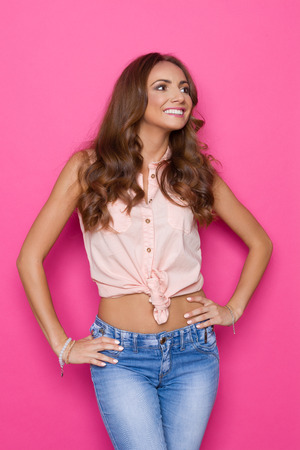 Smiling beautiful young woman in pastel pink shirt posing with hands on hip and looking away. Three quarter length studio shot on pink background. Stock Photo