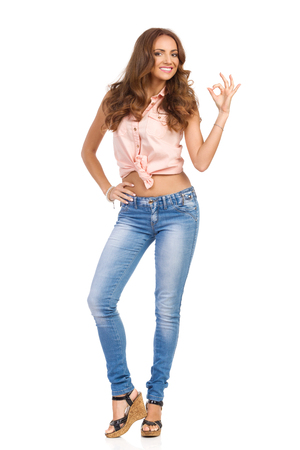 Smiling attractive woman in pink shirt, jeans and cork high heels showing OK sign and looking at camera, Full length studio shot isolated on white.
