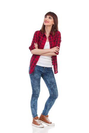 waiting glance: Smiling young woman in red lumberjack shirt, jeans and brown sneakers standing with arms crossed and looking up. Full length studio shot isolated on white.