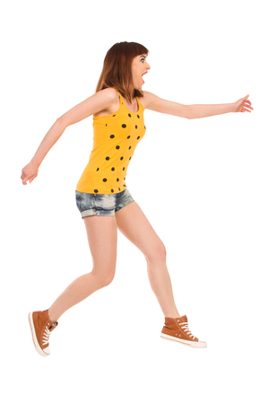 Young woman in yellow dotted shirt, jeans shorts and brown sneakers jumping and shouting. SIde view. Full length studio shot isolated on white.