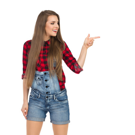lumberjack shirt: Smiling young woman in red lumberjack shirt, jeans dungarees shorts pointing and looking away. Three quarter length studio shot isolated on white.