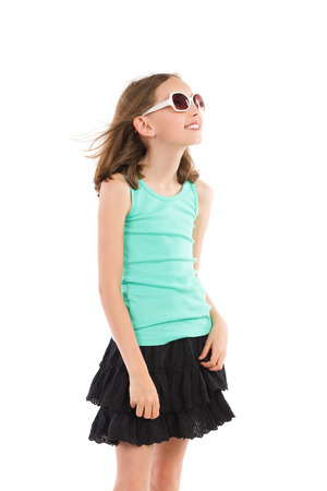 three quarter length: Young girl in teal shirt and black skirt posing in sunglasses and looking away. Three quarter length studio shot isolated on white.