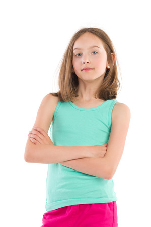 waist shot: Little girl in green shirt posing with arms crossed. Waist up studio shot isolated on white.