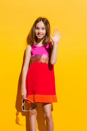 three quarter: Fashionable girl in mini dress waving hand. Three quarter length studio shot on yellow background.