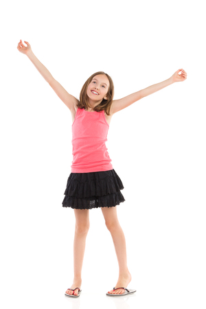 standing up: Smiling little girl with arms raised looking up. Full length studio shot isolated on white.