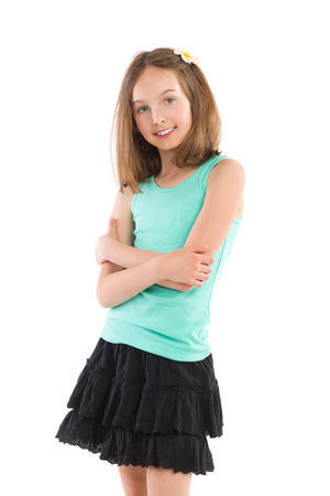 Young girl in teal shirt and black mini skirt posing with arms crossed and smiling. Three quarter length studio shot isolated on white.