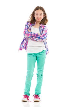lumberjack shirt: Smiling little girl posing with arms crossed, wearing lumberjack shirt and green trousers. Full length studio shot isolated on white.