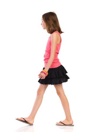 Girl is walking in slippers and mini skirt, side view. Full length studio shot isolated on white.
