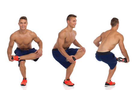Young fit man in blue shorts and orange sneakers crouching on one leg, holding his leg on other leg knee and stretching gluteus maximus. Full length studio shot isolated on white.