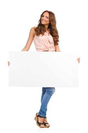 big cork: Smiling attractive woman in pink shirt, jeans, and cork high heels, standing and holding big white poster. Full length studio shot isolated on white.